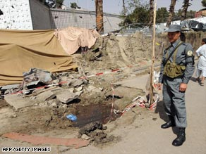 Afghan policemen and health workers carry a dead body after a suicide attack in Kabul, Afghanistan, Monday.