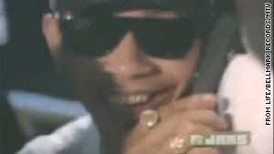 "Conspiracy theorists say the cool cat in the ""Whoomp (There It Is)"" video could be a young Barack Obama."