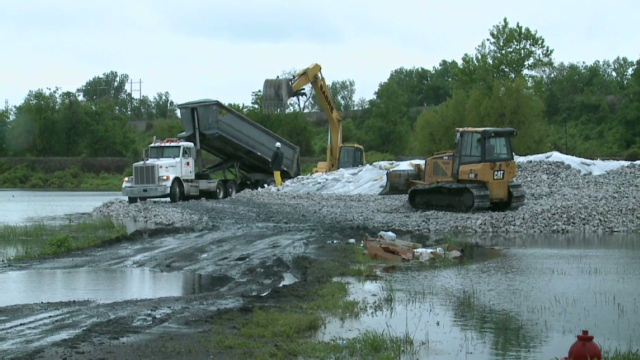 Levee breach lowers river, but record flooding still