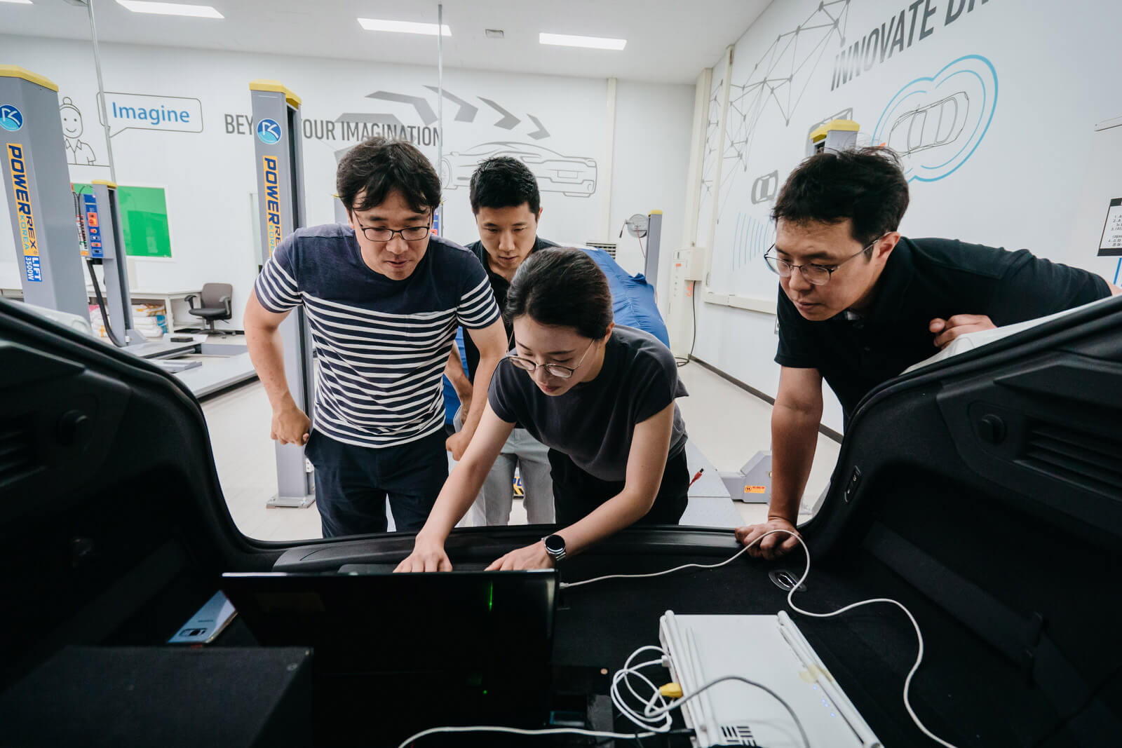 Samsung engineers from the Digital Cockpit Lab update the software of a smart vehicle on a laptop.