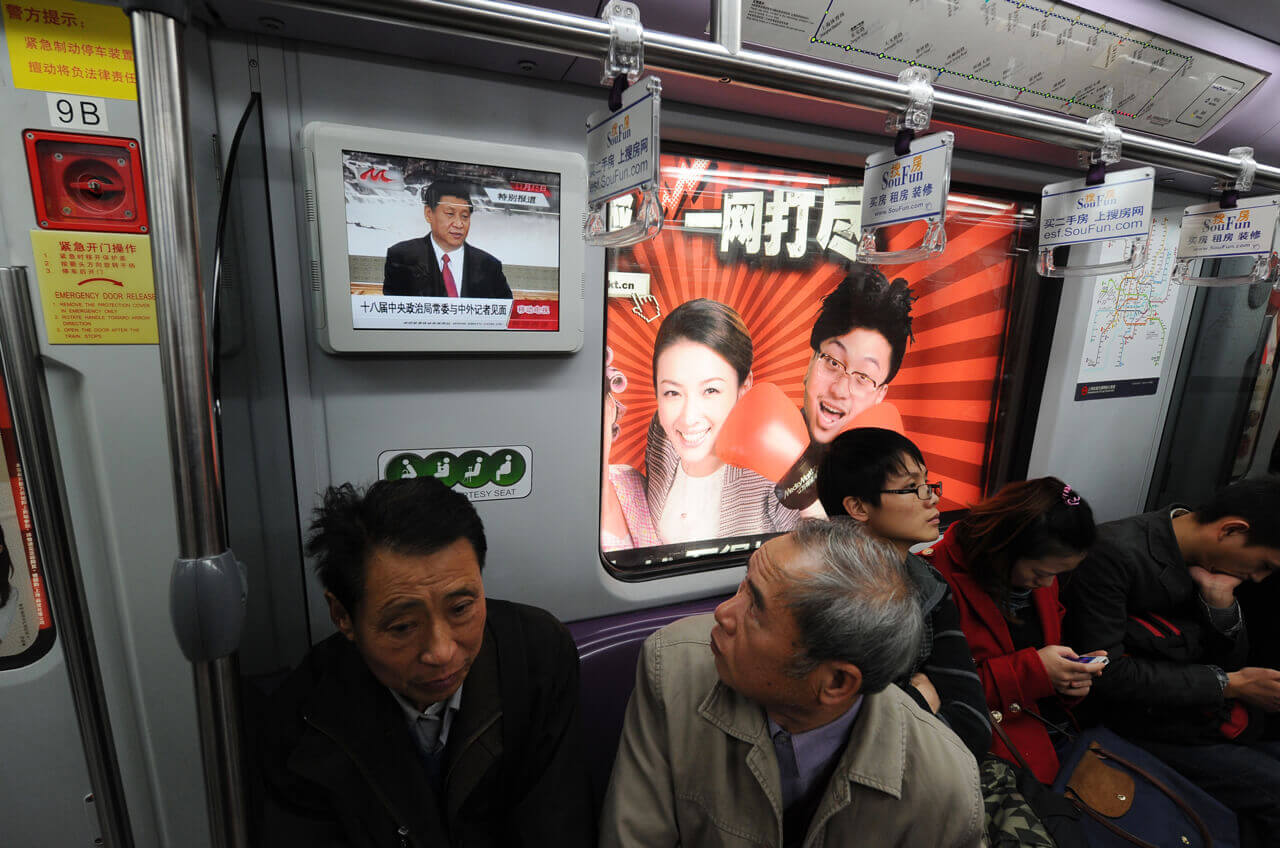 A passenger on a subway train in Shanghai watches a television screen showing Xi Jinping on November 15, 2012, the day he was made general secretary of the CCP.