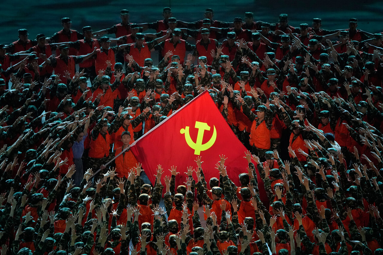 Performers in the role of rescue workers gather around a Communist Party flag during a gala show ahead of the 100th anniversary of the founding of the CCP in Beijing on Monday, June 28, 2021.